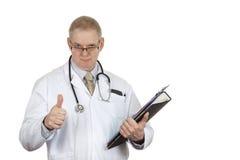 Doctor en los vidrios que llevan de la capa blanca que dan los pulgares para arriba Imagenes de archivo