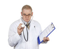Doctor en los vidrios que llevan de la capa blanca que sostienen el estetoscopio Foto de archivo