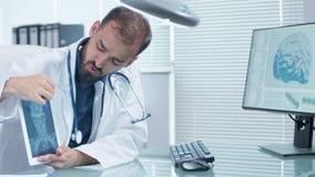 Doctor en oficina del moder con el escritorio de cristal que habla y que se?ala a una pantalla digital de la tableta con un rayo  metrajes