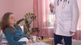 Doctor en temperatura paciente joven de la medida blanca del delantal con el termómetro digital metrajes