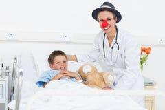 Doctor en traje del payaso con el muchacho en hospital Foto de archivo