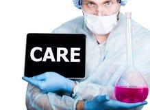 Doctor en uniforme quirúrgico, sosteniendo el frasco rosado y la PC digital de la tableta con la muestra del cuidado tecnología y Imagen de archivo