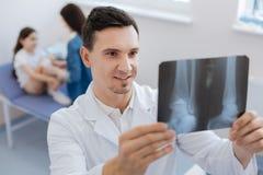 Doctor encantado agradable que es feliz sobre su paciente imagen de archivo