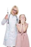 Doctor enojado que hace la inyección vaccínea a un niño Fotos de archivo libres de regalías