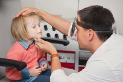 Doctor ENT checking ear with otoscope to girl patient Stock Image