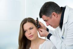 Doctor a ENT que comprueba el oído con el otoscopio al paciente de la mujer Fotos de archivo libres de regalías