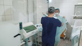 The doctor enters the operating room. A nurse helps to dress a doctor`s gown in the operating room. Preparing for. Surgery. Operating room in the hospital. A stock video