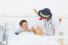 Doctor entertaining sick boy in hospital bed Royalty Free Stock Photo