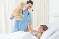 Doctor entertaining sick girl with teddy bear Stock Photos