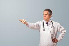 Doctor envejecido centro que gesticula con el espacio de la copia Fotografía de archivo
