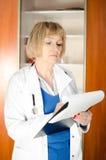Doctor envejecido medio de la mujer que toma notas Foto de archivo libre de regalías