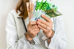 Doctor with euro money and handcuffs - bribe concept. Doctor with euro money and handcuffs - corruption and bribe concept in medicine Stock Image