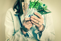 Doctor with euro money and handcuffs - bribe concept. Doctor with euro money and handcuffs - corruption and bribe concept in medicine - retro style Stock Images