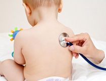 Doctor exam. Children's doctor exams infant with stethoscope royalty free stock image