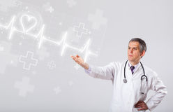 Doctor examinates heartbeat with abstract heart Stock Photo
