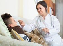 Doctor examinating el muchacho adolescente con quinsy en casa Imagenes de archivo
