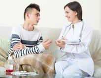 Doctor examinating el muchacho adolescente con quinsy en casa Fotos de archivo