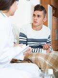 Doctor examinating el muchacho adolescente con quinsy en casa Fotografía de archivo