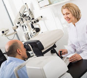 Doctor examinating eye with aid of slit lamp Stock Photos