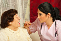 Doctor examine elderly for sore throat. Doctor women examine elderly patient for sore throat in her house stock photos