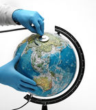 Doctor examine globe. Doctor examine with stetoscope the ill Earth Stock Images