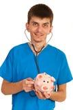 Doctor examine piggybank Royalty Free Stock Photos