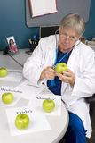 Doctor examines an apple. A doctor examines an apple with his stethoscope. Image is useful for any healthy diet or eating inference royalty free stock photography