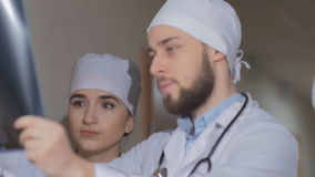 Doctor examines a colleague of x-ray image and explains that it is necessary to appoint a patient stock footage