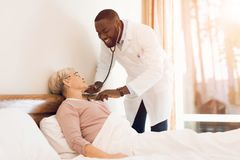 The doctor examines an elderly patient in a nursing home. She lies in bed and talks to him. He measures her pulse and pressure. She complains about his Royalty Free Stock Photos