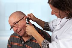 Doctor examines ears with otoscope. Doctor examines the inner of the ears of her patiënt with an otoscope royalty free stock images