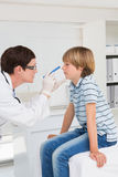 Doctor examines little boy with a light Stock Photo