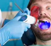 Doctor examines the oral cavity on tooth decay. Caries protection. Tooth decay treatment. Dentist working with dental. The reception was at the female dentist Stock Photo