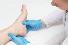 Doctor examines the patient`s leg with heel spurs, pain in the foot, white background, close-up, plantar fasciitis royalty free stock photography