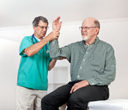 Doctor Examines Patient's Wincing with Pain in Arm. Male doctor, surgeon or nurse examines a senior man's arm. Patient is in obvious discomfort, wincing in pain Royalty Free Stock Images