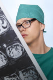 Doctor examines X-ray human brain. Male doctor examines X-ray picture of a human brain Royalty Free Stock Photo