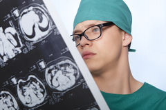 Doctor examines X-ray human brain. Male doctor examines X-ray picture of a human brain Royalty Free Stock Images