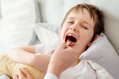 Doctor examines sick boy throat Stock Image