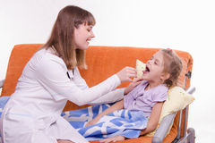 The doctor examines the throat Sick little girl in bed Stock Image