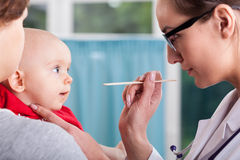 Doctor examining baby with spatula Stock Image