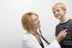 Doctor Examining Boy. Happy female doctor examining Caucasian boy with stethoscope in clinic stock photos