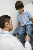 Doctor Examining Boy With Reflex Hammer Royalty Free Stock Photo
