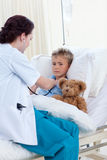 Doctor examining a boy's chest Royalty Free Stock Images