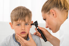 Doctor Examining Boy`s Ear. Close-up Of Female Doctor Examining Boy`s Ear With An Otoscope Stock Image