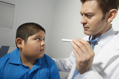 Doctor examining boy's eye Stock Image