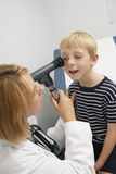 Doctor Examining Boy's Eye. Female doctor examining young boy's eye stock photography
