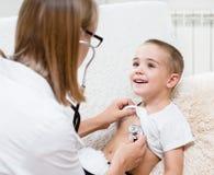 Doctor examining boy with stethoscope Royalty Free Stock Photo