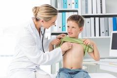 Doctor examining boy with stethoscope Royalty Free Stock Photos