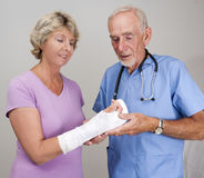 Doctor examining cast on senior woman's arm royalty free stock image