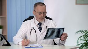 Doctor examining chest lung x-ray, filling patients medical form, flu epidemic stock photo