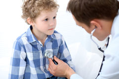Doctor examining a child  patient by stethoscope Stock Photography